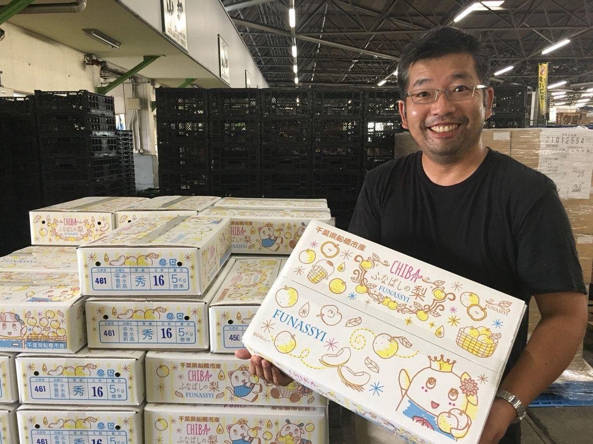 2018年の梨箱を手にニッコリする船橋市場の「梨おじさん」