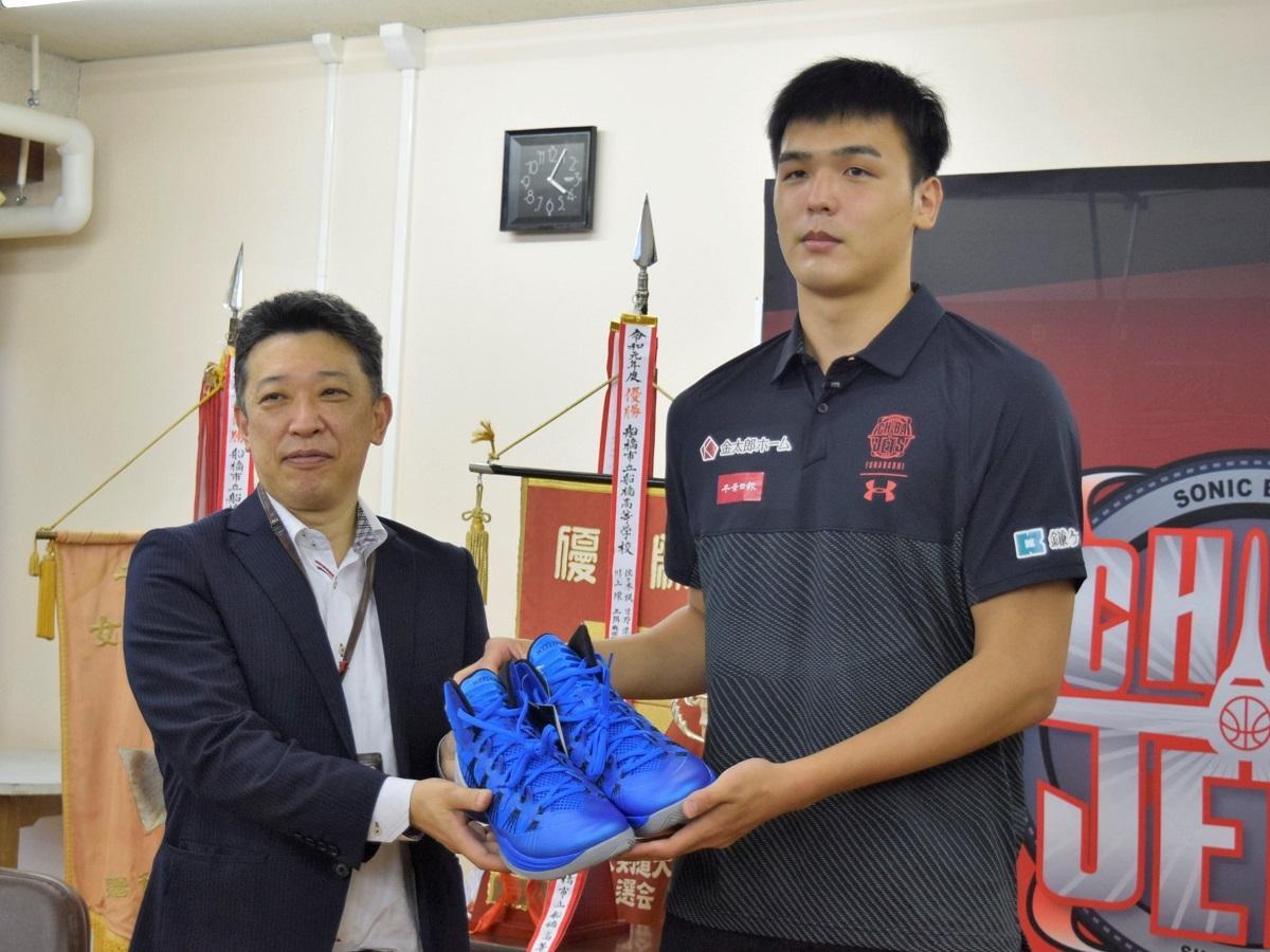 寄贈する赤穂選手サイン入り34cmの靴を持って、恩師である近藤教頭先生と
