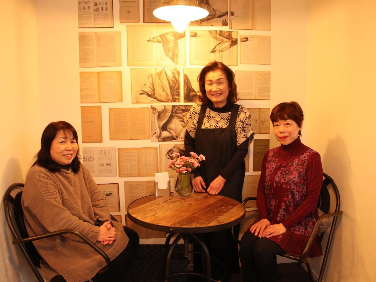 店主の長島和子さん(中央)を挟んで常連客の二人。お気に入りの壁紙のスペースで