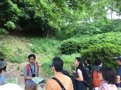 伏見城の堀跡で説明するガイドの梅林さんと聞き入るツアー参加者