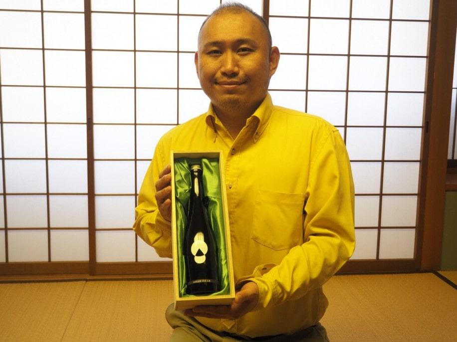 玉露の出品茶を抽出した最高級ボトリングティー「神秘の雫(しずく) 宇治玉露・YASUNORI」を持つ北川さん