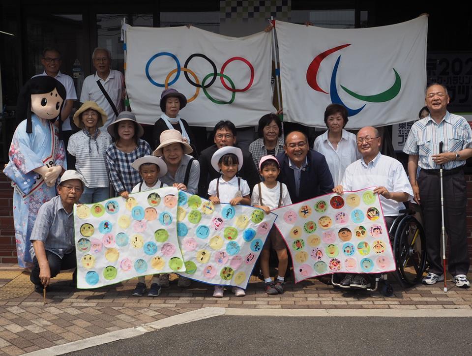 オリンピック・パラリンピック旗と中小路長岡京市長ら関係者