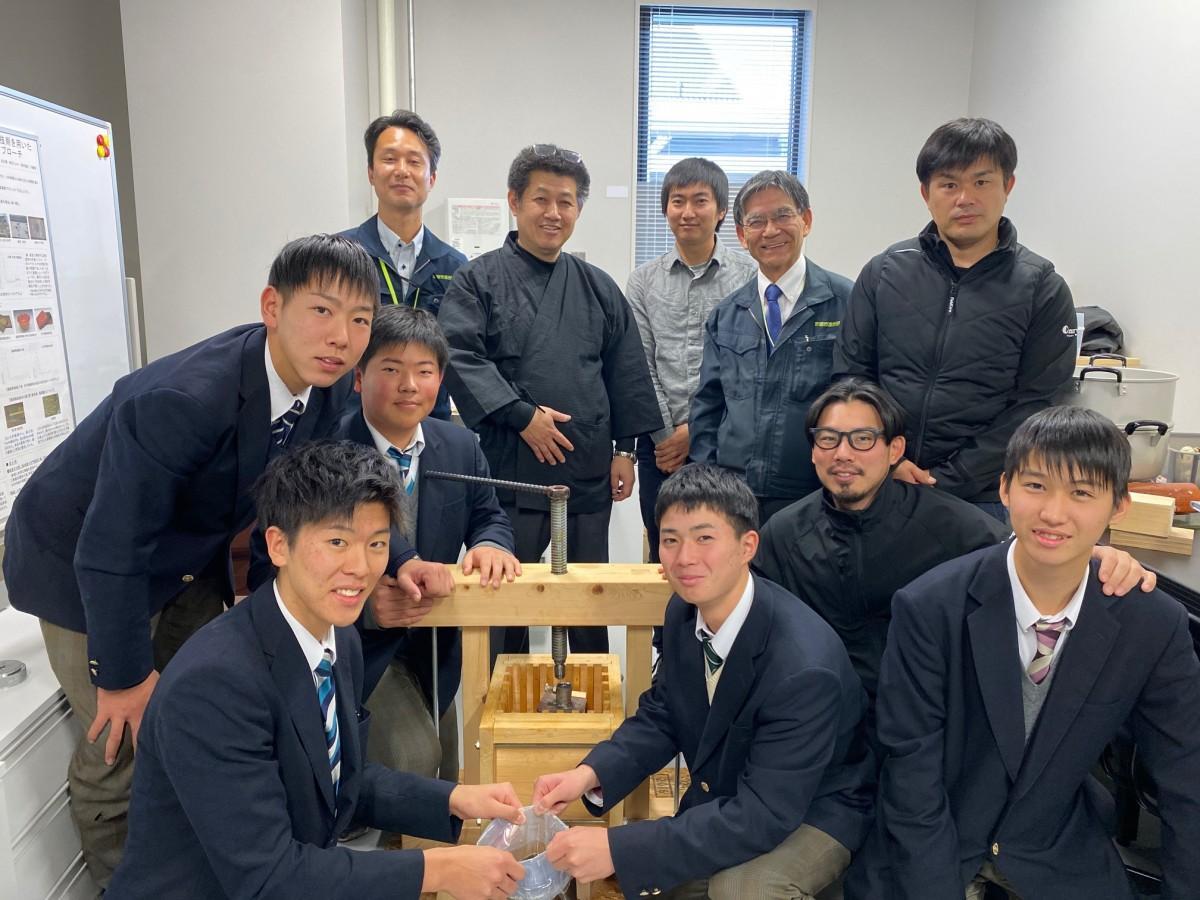 和ろうそくの原材料を搾る機器を再現した北桑田高校の生徒と中村ローソクの田川さんら