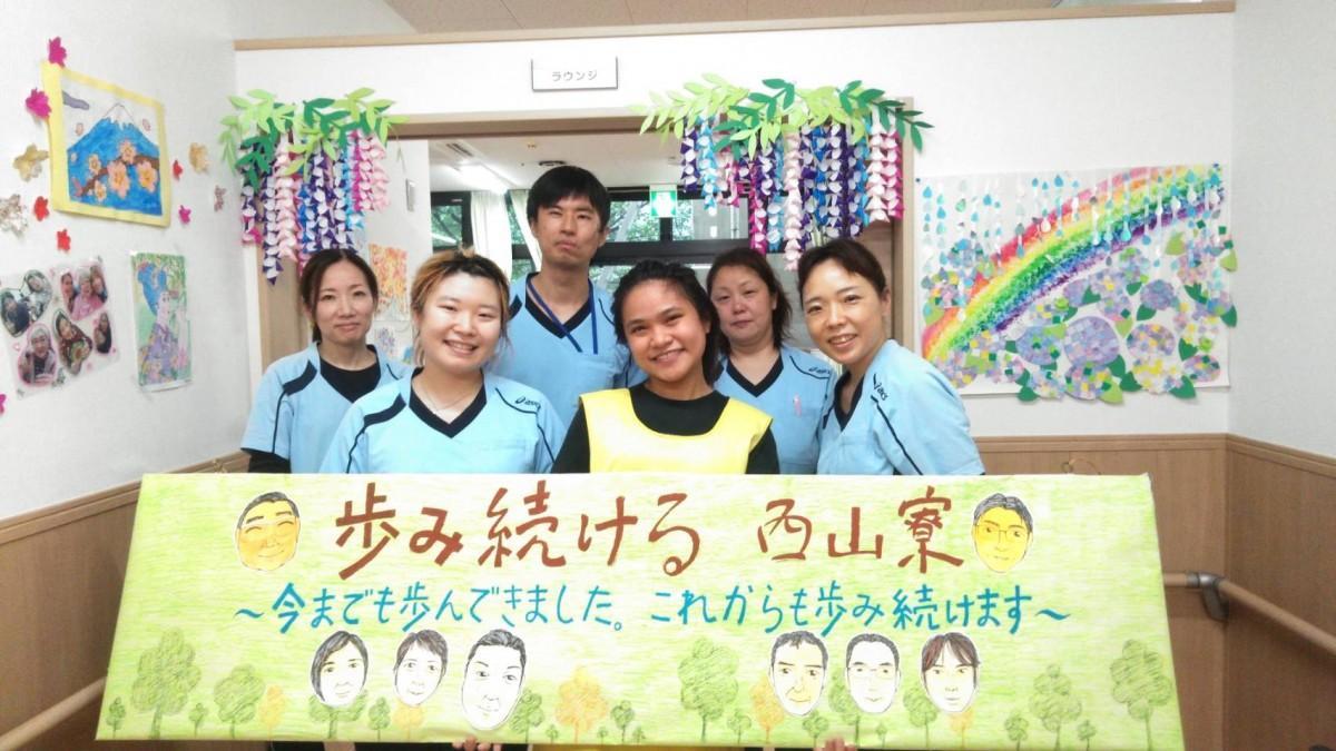 介護分野では京都府内で初の特定技能1号を取得したハニーシャイラ・オショネスさん(全列中央の黄色のエプロン姿)