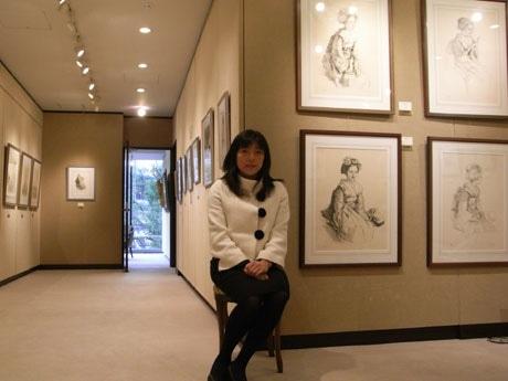 野呂洋子副社長。1月末まで開催していた「小磯良平版画展」の作品をバックに
