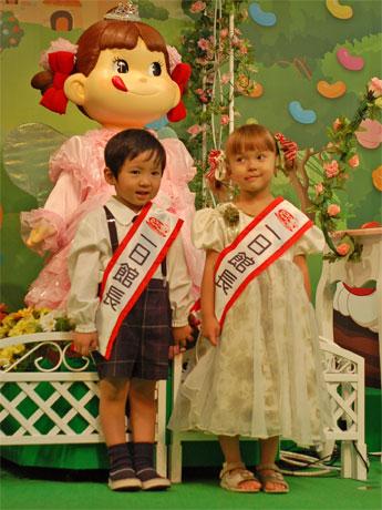 「ペコちゃんロボット」を背に、ペコちゃんさながらの表情の高橋ジュリアちゃん(右)と、リアル「ポコちゃん」の菅俊輔くん(左)