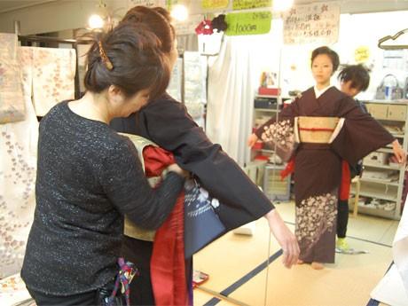 黒い訪問着に赤い帯揚げ、帯締めを合わせ、素早くモデルを着付けていく藤田さん