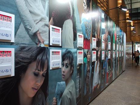 長さ約11メートル、高さ約3メートルのポスター群。各ポスターには「いいね!」ボタンも