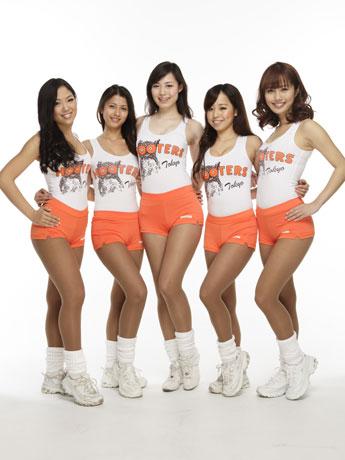タンクトップとオレンジ色のホットパンツのコスチューム姿のフーターズガール。画面中央が「2012年ミスフーターズジャパン」のMayuさん