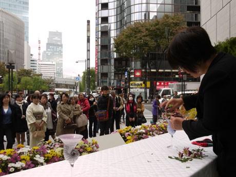 数寄屋橋交差点を前に花を生ける小原流・伊藤庭花さん