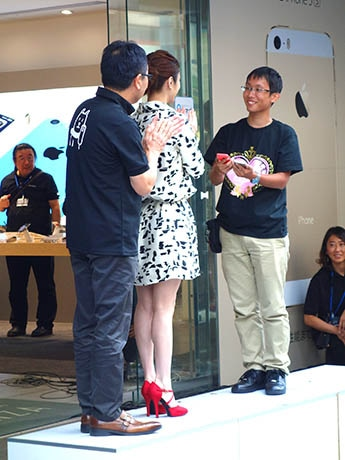 宮内謙副社長と上戸彩さんから購入したiPhone新機種を受け取る井上拳斗さん
