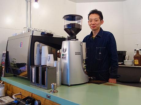 オーナーの川崎清さんとエスプレッソマシン。ドアで作ったカウンターにはドアノブが