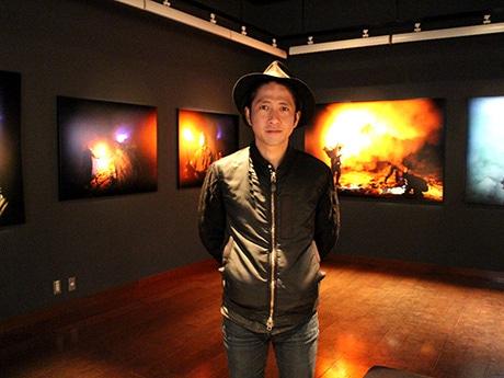 「名越啓介写真展:BLUE FIRE」の会場に立つ名越さん