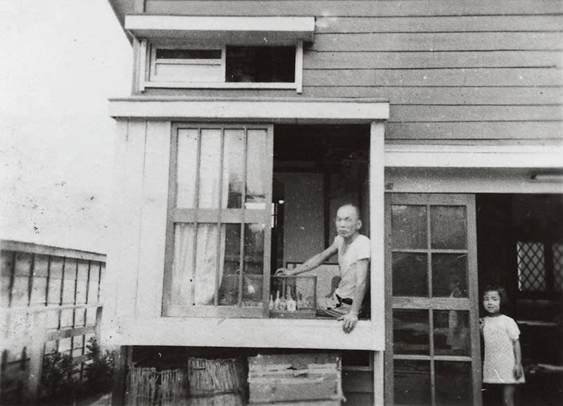 「12坪の家」書斎の出窓に腰掛ける吉田謙吉と居間兼ホール入り口に立つ娘・珠江(1949年夏)写真提供:吉田鹿乃子