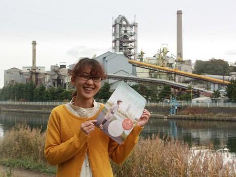 八戸セメントをバックにイベントへの参加を呼び掛ける大澤苑美さん