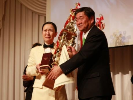 優勝トロフィーを手に感極まる茂内真利子(左)さんと、プレゼンターの小林眞八戸市長