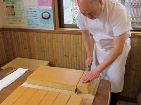 カステラを解体する戸田菓子舗店主の戸田和博さん
