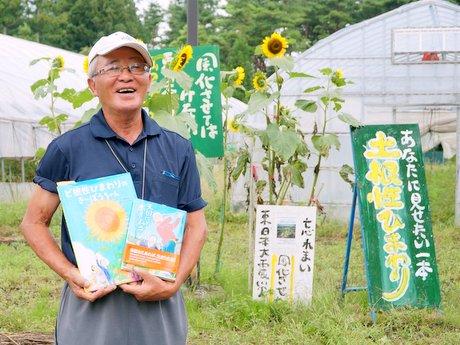石巻から譲り受けた「ど根性ひまわり」の花と「山の楽校」岩崎光宏校長