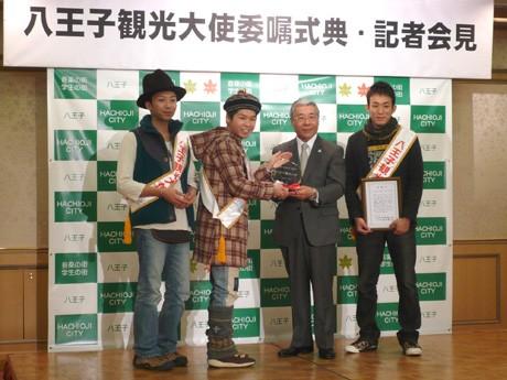 黒須市長から委嘱状とクリスタルの盾、名刺とたすきを渡されたメンバー