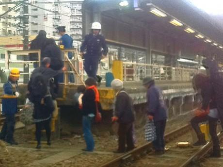 JR高尾駅前で緊急停車した電車から駅のホームに避難する人たち