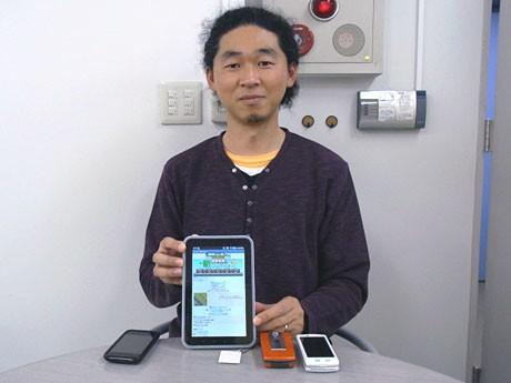 「全駅制覇!駅コレクション」を表示したタブレット端末を持つ電波の杜の炭谷大輔社長