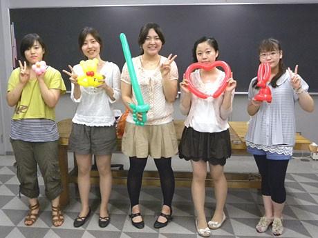 自ら作ったバルーンアートを持つ「ばろん。」代表の小室さん(中央)とメンバー