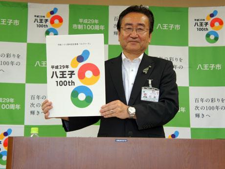 ロゴマークを掲げる石森孝志八王子市長