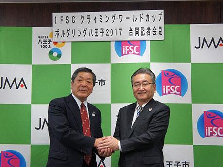 握手をする日本山岳協会の尾形好雄副会長(左)と石森孝志八王子市長(右)