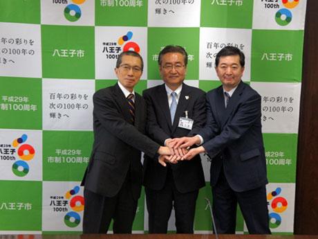握手する石森孝志八王子市長(中央)と川名明夫拓殖大学学長(左)、エイビットの檜山社長(右)