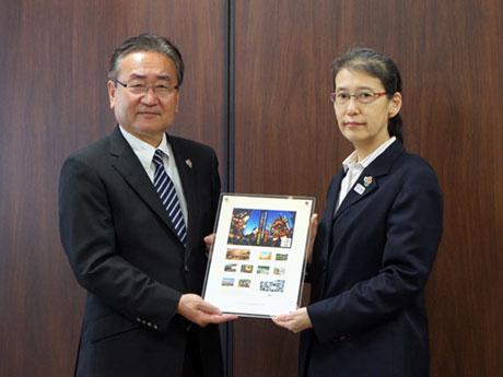 山崎支社長(右)から石森市長に切手が手渡された