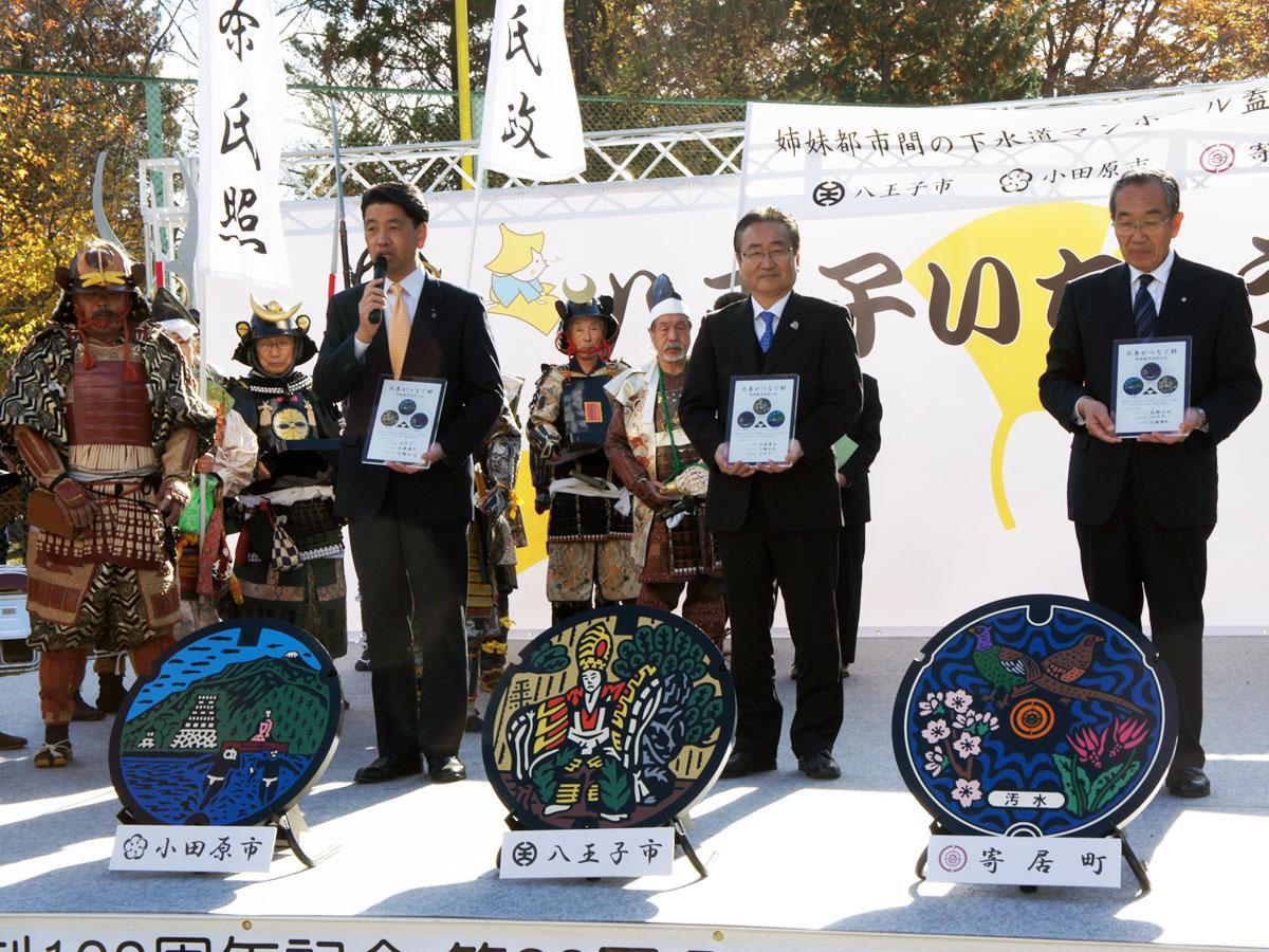 記念パネルを持つ石森孝志八王子市長(中央)、加藤憲一小田原市長(左)、花輪利一郎寄居町長