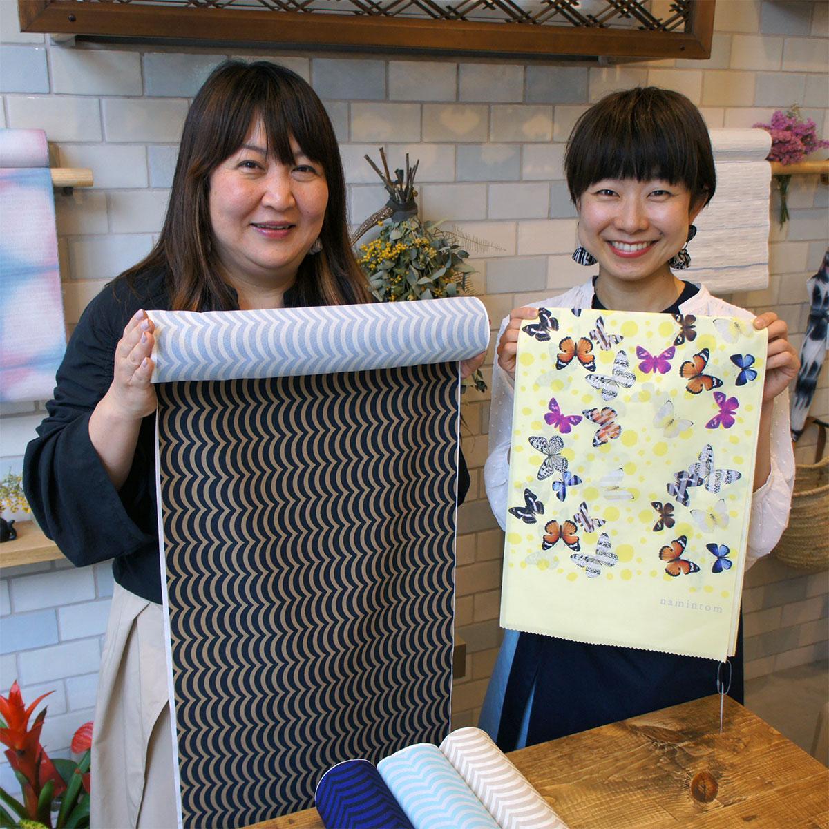 自社ブランドのオリジナル商品を持つ坂本さん(左)