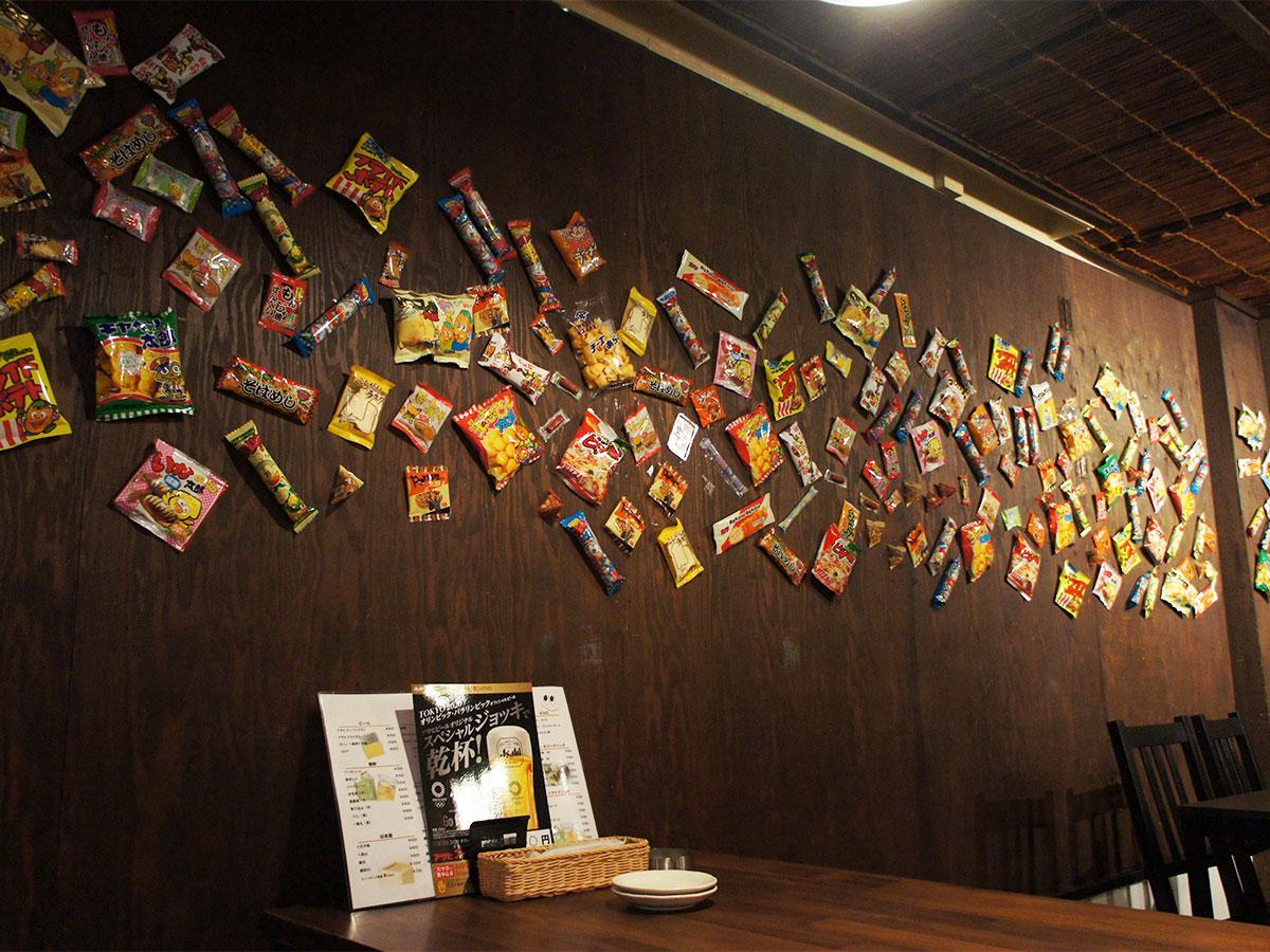 壁に駄菓子が貼り付けられている「居酒屋にっこり」