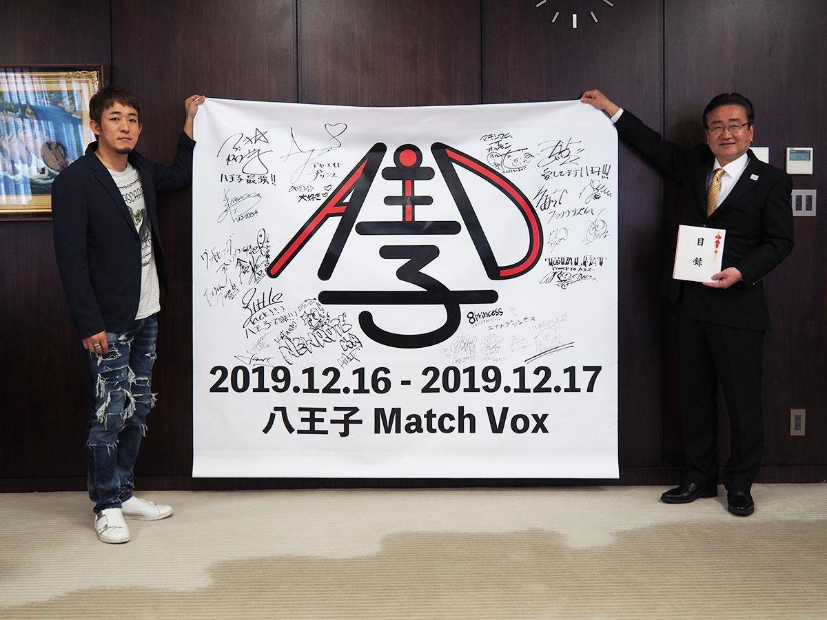 ステージに飾られたバックドロップを持つファンキー加藤さん(左)と石森市長