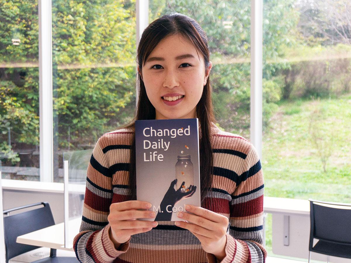 発売された小説「Changed Daily Life」を手にする坂本さん