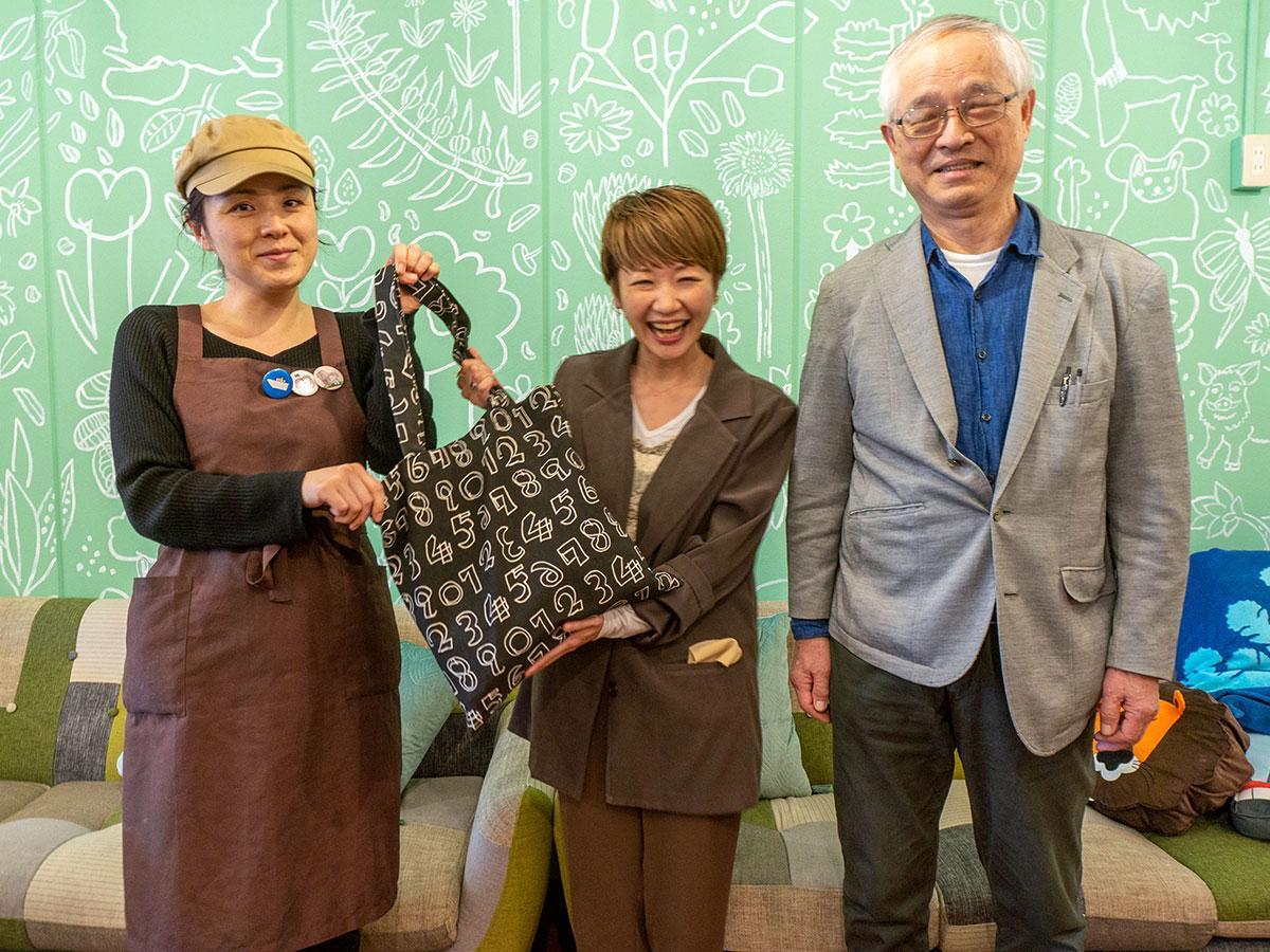 完成したトートバッグを手にするYORIKOさん(写真中央)と「しあわせのたね」の和田隆夫理事長(右)