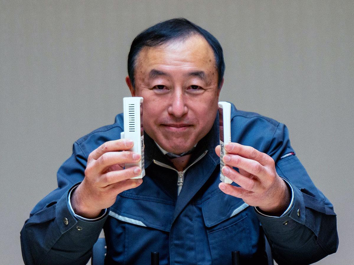 開発した「5Gガラケー」(左)と、1月に発表した自営PHS端末の厚さの違いを示す小林さん