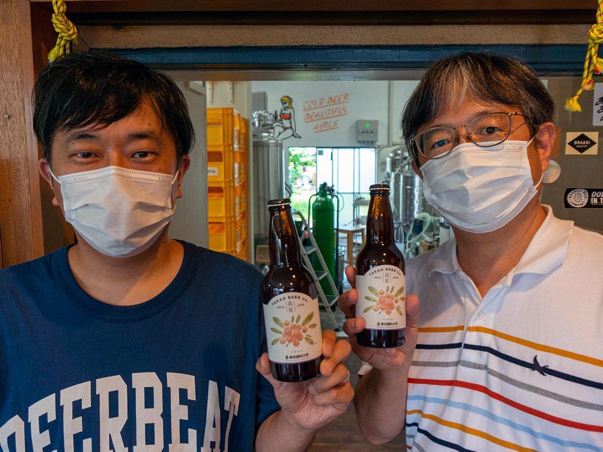 完成したビールを手にする東京薬科大学の志賀助教(写真右)と高尾ビールの池田さん