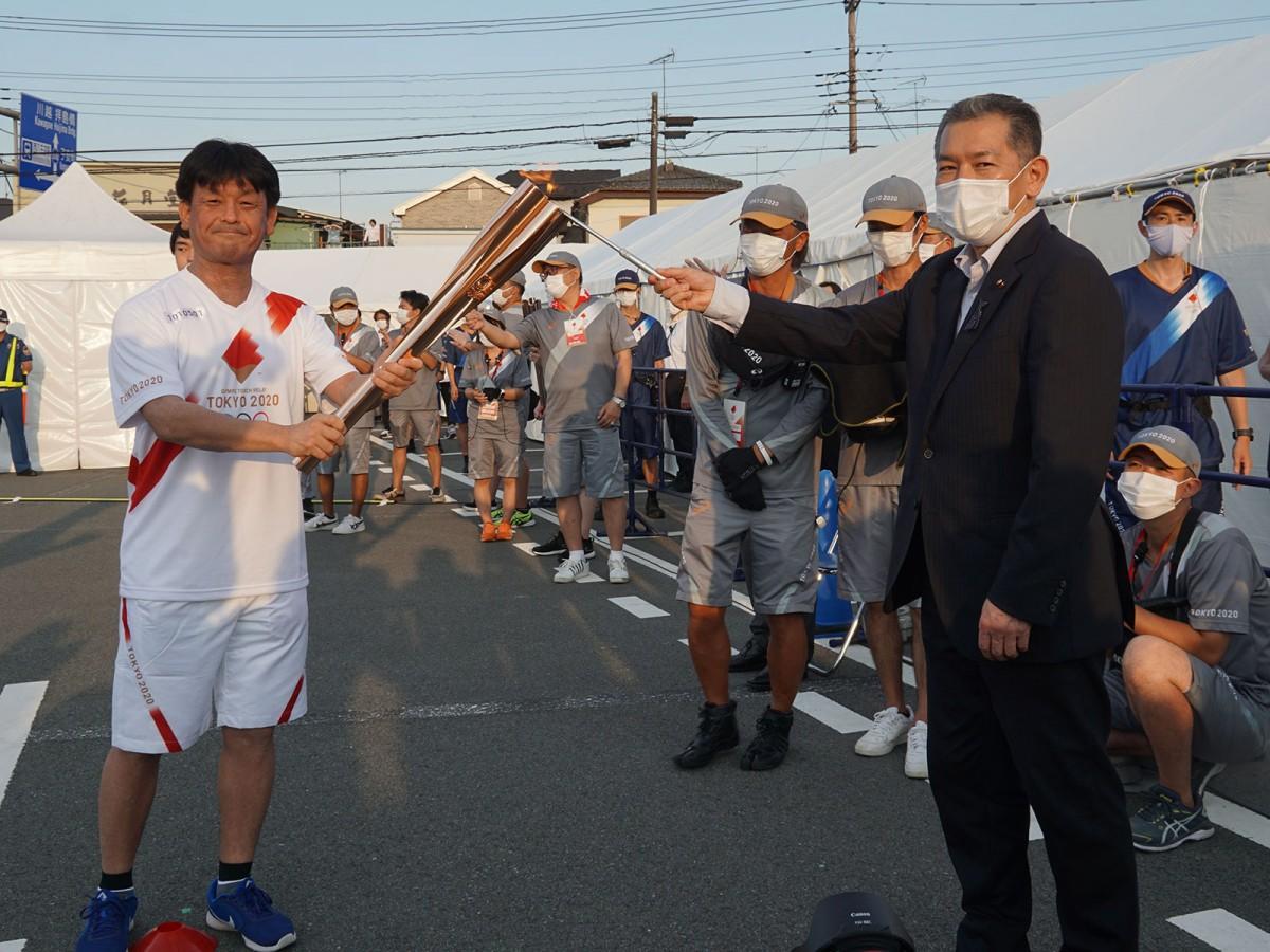 ランタンから取り出した聖火は、八王子市議会議長の吉本孝良さんから区間1人目の荒木一彦さんへ。