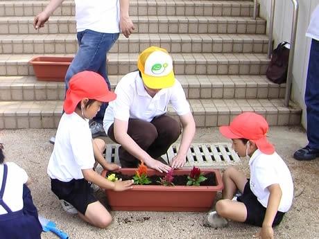 小学生らと一緒に花を植えるふくやの社員。(久留米市竹野小学校)