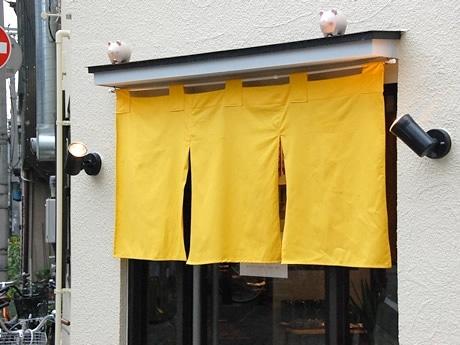 黄色いのれんの上には、かわいいブタの飾りが2つ。