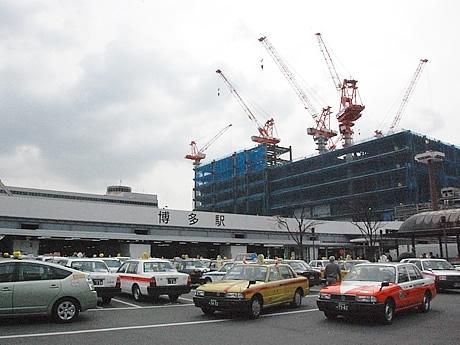 現在の博多駅口のタクシープール。新駅ビルの阪急百貨店は6~7階部分まで骨組の工事が進んでいるのがうかがえる。