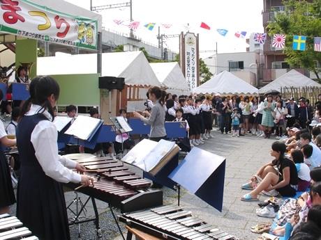 昨年の地元中学の演奏の様子。商店街には露店が数多く並び、多くの人が訪れる。