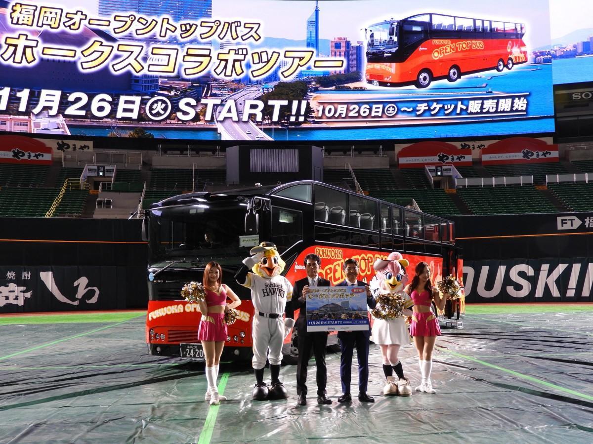 ヤフオク!ドームで福岡オープントップバス「ホークスコラボツアー」お披露目式の様子。中央に西日本鉄道 取締役 常務執行役員の清水信彦さん(右)と、福岡ソフトバンクホークス 取締役 兼執行役員の吉武隆さん