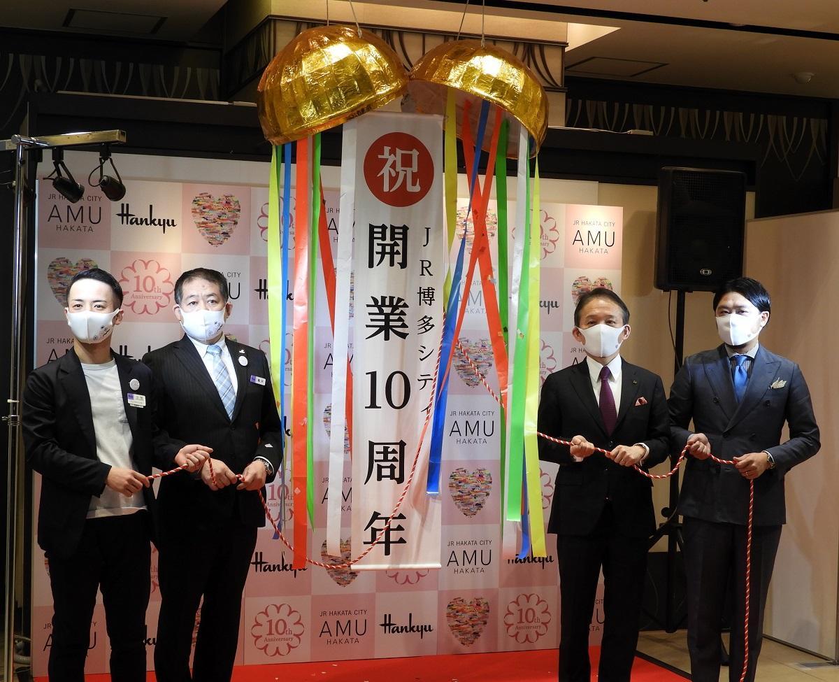くす玉割りの様子 JR博多シティ社長の前田勇人さん(右から2人目)、博多阪急店長の亀井潤一さん(左から2人目)など