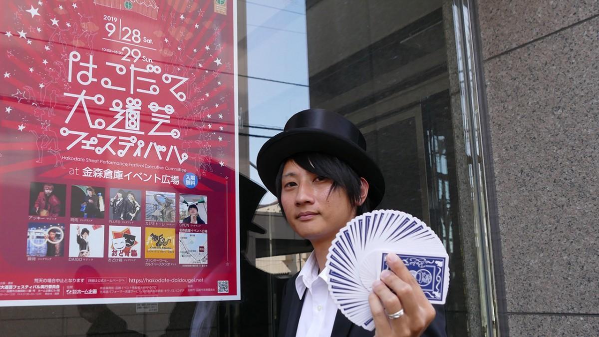 フェスティバルのポスターの前に立つ主催者でマジシャンの高野太吾さん