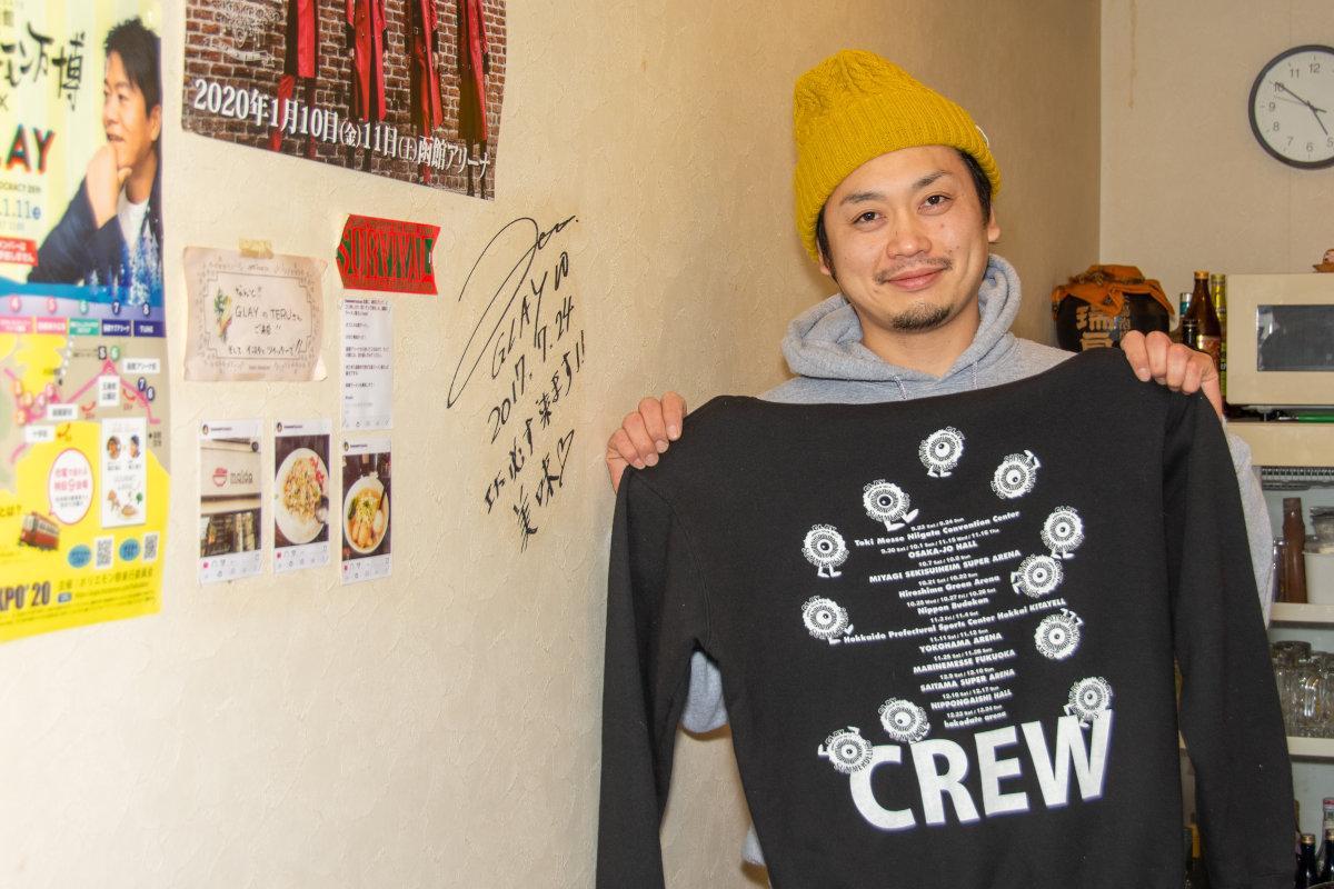 前回のGLAY函館アリーナライブの際に関係者から贈られたスタッフ用パーカを掲げる