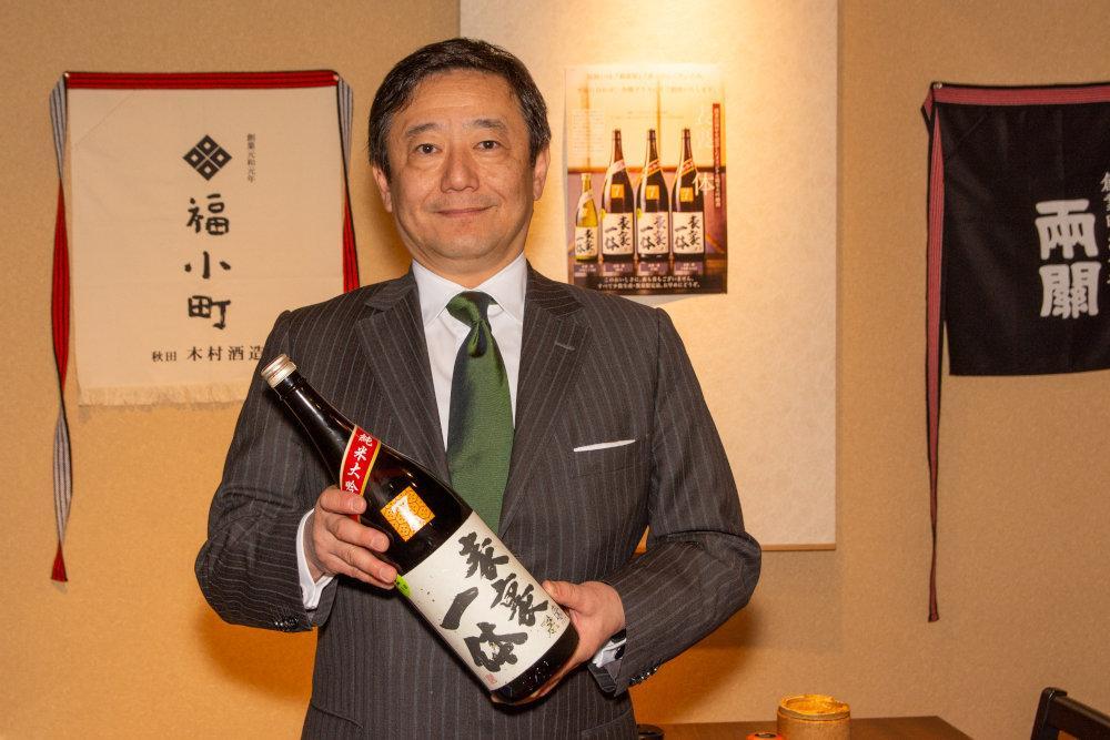 オリジナル日本酒「表裏一体」を手に来店を呼びかける社長の岸部悟司さん