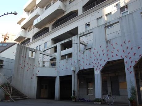 寿町総合労働福祉会館壁面に制作中の浦田琴恵さんの作品「永遠の開拓者たち」