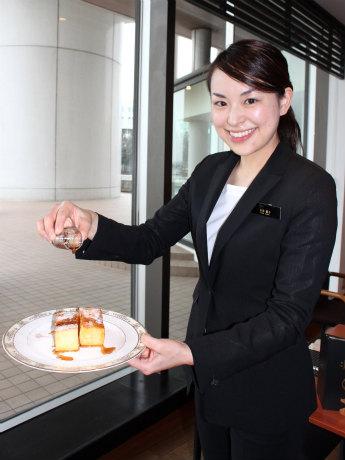 「究極のフレンチトースト」にメープルシロップを注ぐヨコハマ グランド インターコンチネンタル ホテルの川井優子さん